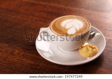 Delicious aromatic cappuccino in a white porcelain cup with a biscuit on the side on a wooden table. Image contains copy space. - stock photo