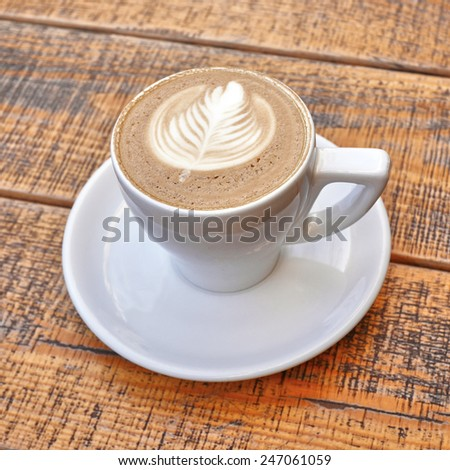 delicious art cappuccino coffee cup on wooden background - stock photo