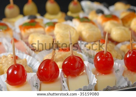 Delicious assorted appetizers. Cherries with cheese in focus