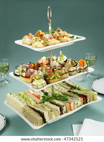 Delicious assorted finger food and sandwiches on a three tier stand. - stock photo