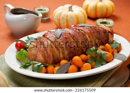 Delicious bacon-wrapped turkey breast roulade garnished with Brussels sprouts, tomatoes, and Parisian carrots.  - stock photo