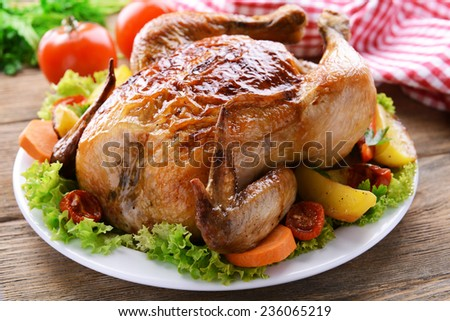 Delicious baked chicken on plate on table close-up - stock photo