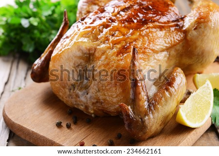 Delicious baked chicken on table close-up - stock photo