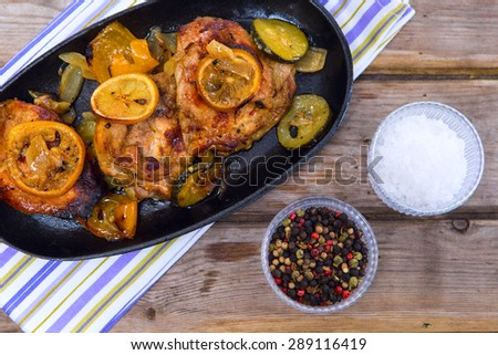 Delicious baked chicken thighs with lemon slices, onion and zucchini served in cast-iron frying pan on rustic wooden table - stock photo