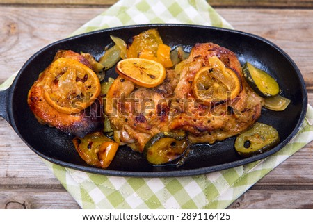 Delicious baked chicken thighs with lemon slices, onion and zucchini served in cast-iron frying pan on rustic wooden table above view - stock photo