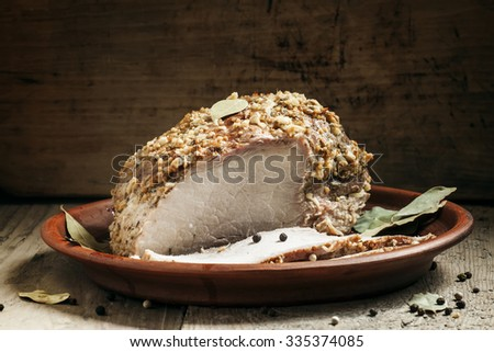 Delicious baked ham pork on a clay tray on the old wooden background, selective focus