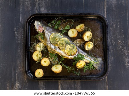 Delicious baked rainbow trout straight from the oven with potato, lemon and herbs. - stock photo