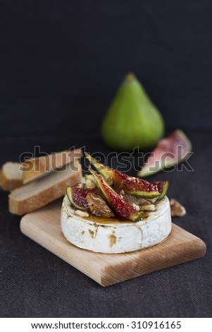 Delicious baked soft brie cheese with figs, walnuts, maple syrup and ciabatta bread slices on a wooden cutting board. Vertical shot on a dark background and dark table cloth. - stock photo