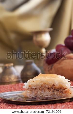 Delicious baklava dessert in oriental golden setting - stock photo