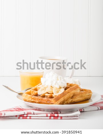 Delicious banana waffles with maple syrup and whipped cream.