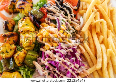 Delicious barbecue  chicken with a side dish of vegetables and potatoes fries. - stock photo
