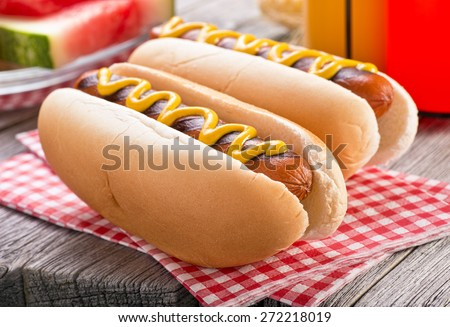 Delicious barbecued hot dogs on a rustic picnic table. - stock photo