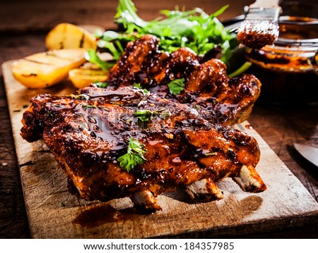Delicious barbecued ribs seasoned with a spicy basting sauce and served with chopped fresh herbs on an old rustic wooden chopping board in a country kitchen - stock photo