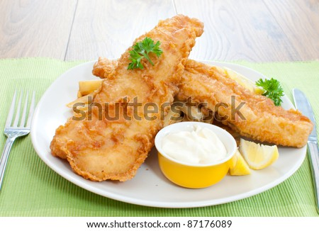 Delicious battered fish on a plate with chips - stock photo