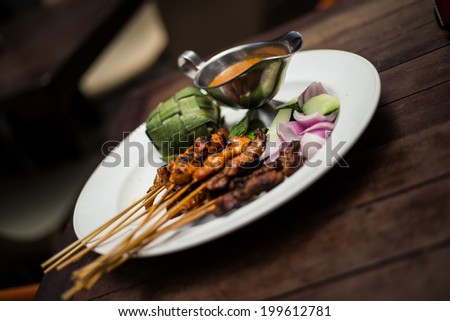 Delicious BBQ cooked skewers of chicken and beef with satay sauce and rice wrapped in leaves - stock photo