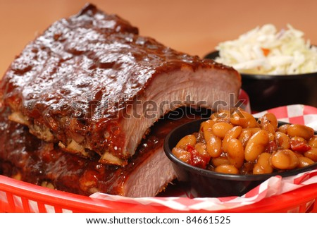 Delicious BBQ ribs with beans, cole slaw and a tangy BBQ sauce - stock photo