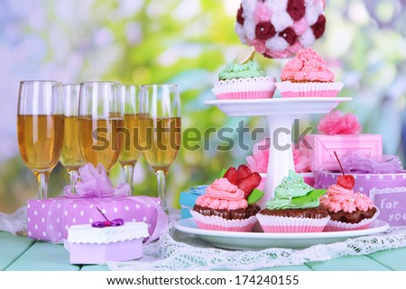 Delicious beautiful  cupcakes on festive table on natural background