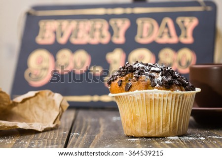 Delicious beautiful tasty muffin with chocolate crumb in paper case on background of cafe work schedule wooden sign board break time pleasure place for lunch indoor closeup, horizontal picture - stock photo