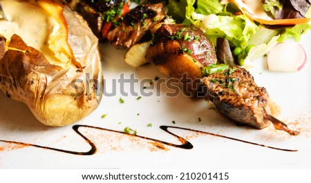 Delicious beef and duck kebab with fresh green salad, baked potato and French pepper cream sauce. - stock photo
