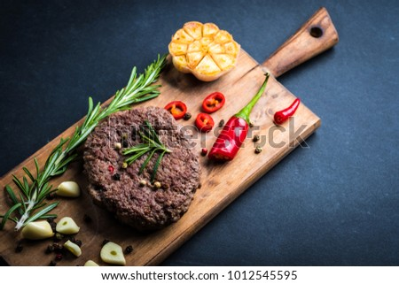 Delicious beef burger steak with spices and herbs on cutting board and slate background