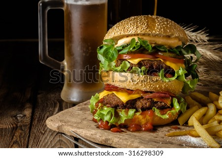 Delicious beef burger with chips and beer on wooden table