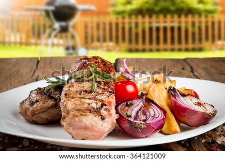 Delicious beef steak and vegetable on wooden table with garden background