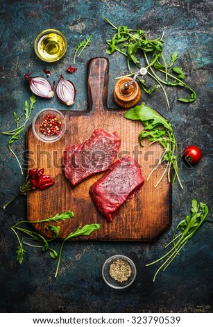 Delicious  beef steak on vintage cutting board with fresh various ingredients for tasty cooking on rustic wooden background, top view. - stock photo