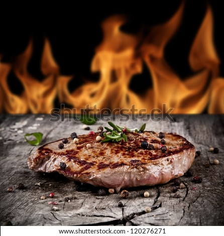Delicious beef steak on wood with flames on background - stock photo