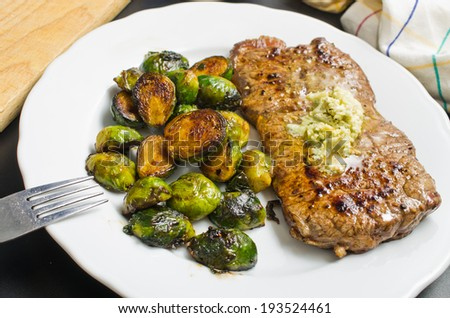 Delicious beef steak with garlic butter and brussel sprouts - stock photo