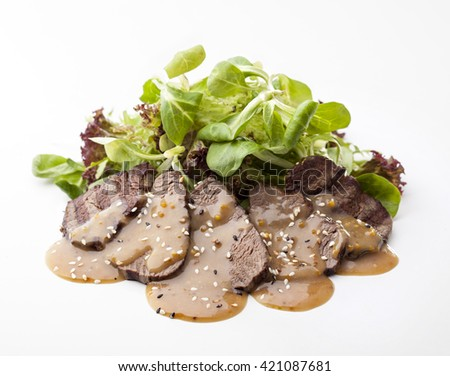delicious beef steak with green salad and sauce on a white background - stock photo