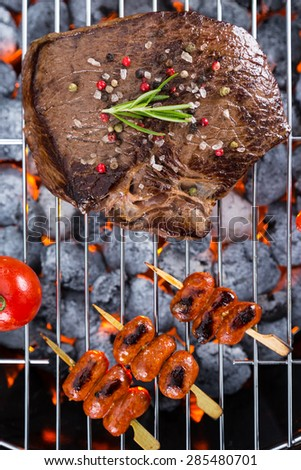 Delicious beef steak with sausages on grill - stock photo