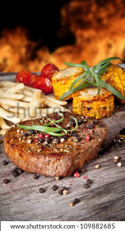 Delicious beef steak with vegetable on wooden table - stock photo