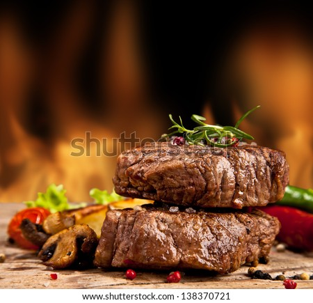 Delicious beef steakes on wood - stock photo