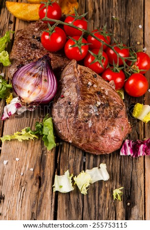Delicious beef steakes on wooden table - stock photo