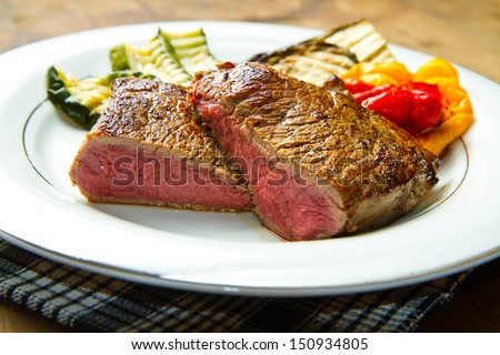Delicious beef steaks on white dish with grilled vegetables - stock photo