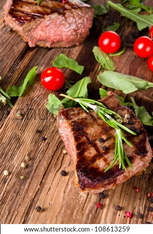 Delicious beef steaks on wooden planks - stock photo