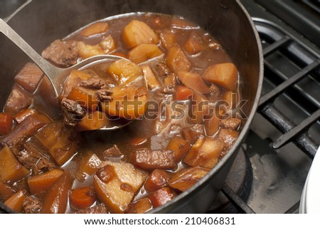Delicious beef stew cooking in a pot in a rich gravy with potatoes and carrots for a traditional Lancashire Hotpot - stock photo