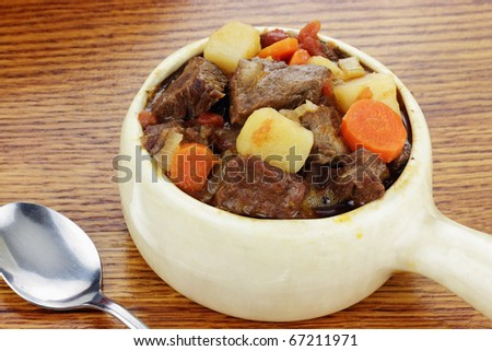 Delicious beef stew served in an onion soup crock with spoon. - stock photo
