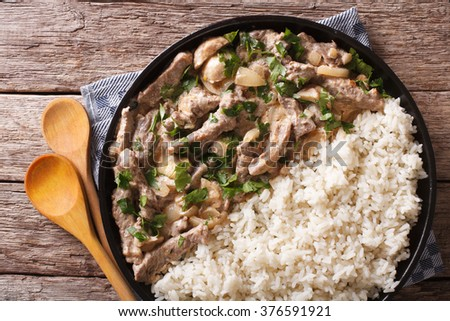 Delicious beef stroganoff with rice close-up on a plate on the table. horizontal view from above