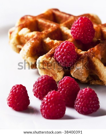 Delicious Belgian waffles garnished with fresh raspberries - stock photo