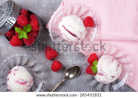 Delicious berry ice cream on glass plate decorated with fresh raspberries on vintage gray background. Top view.  Party concept. - stock photo