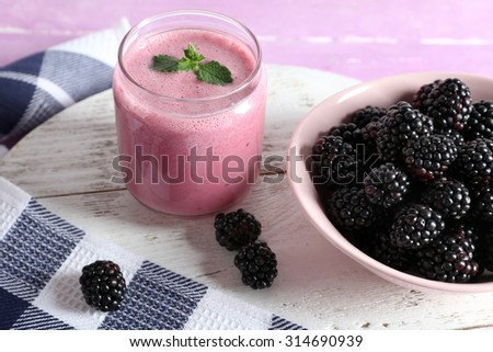 Delicious berry smoothie with blackberries on table close up