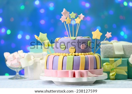 Delicious birthday cake on shiny blue background - stock photo