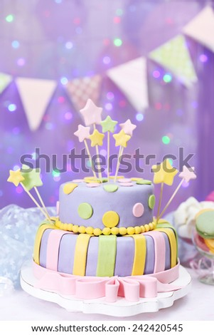 Delicious birthday cake on shiny purple background - stock photo