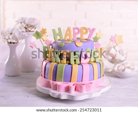 Delicious birthday cake on table on brick wall background - stock photo