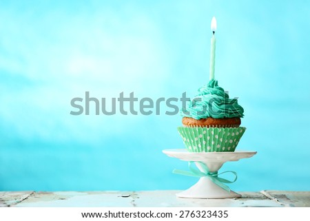 Delicious birthday cupcake on blue background - stock photo
