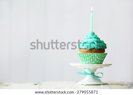 Delicious birthday cupcake on light background - stock photo