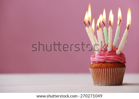 Delicious birthday cupcake on pink background - stock photo