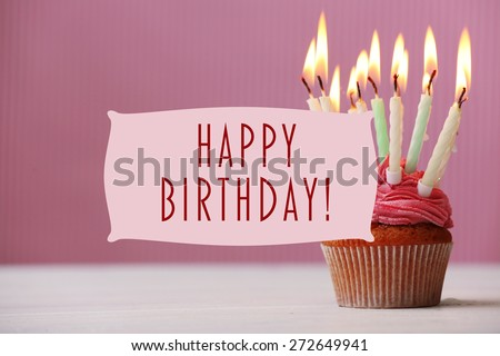 Delicious birthday cupcake on pink background