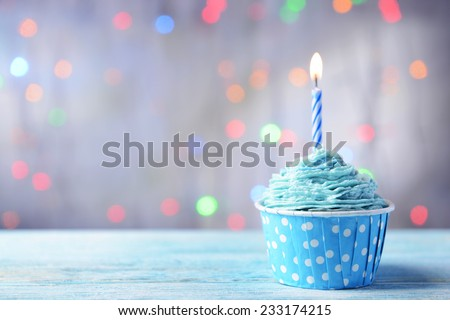 Delicious birthday cupcake on table on light background - stock photo